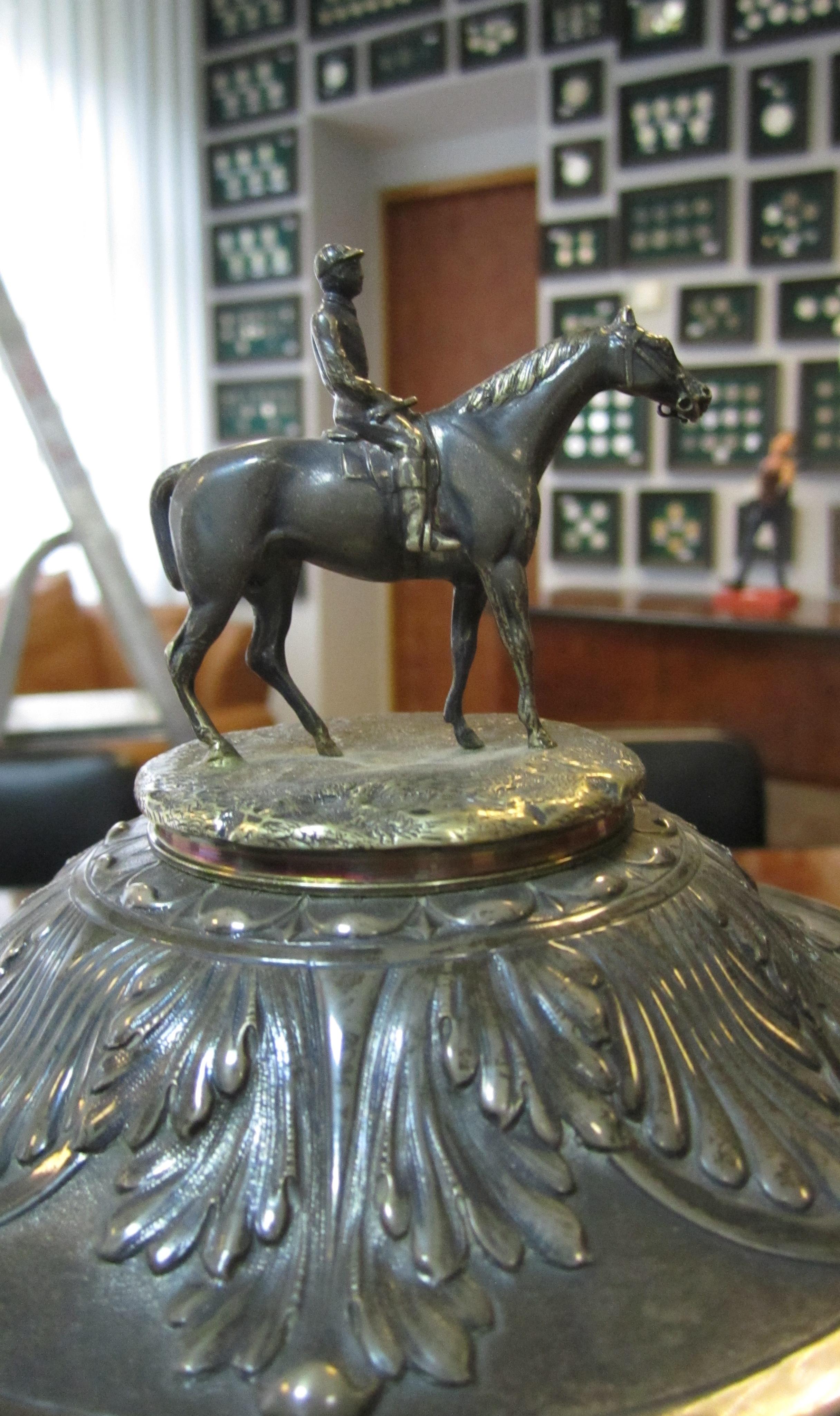 Чашка  виготовлена зі срібла 800 проби. Прикрашена позолоченою фігурою жокея на коні, чеканним зображенням скачок та орнаментом. Клейма на кришці f.M. , інв.№ 56242