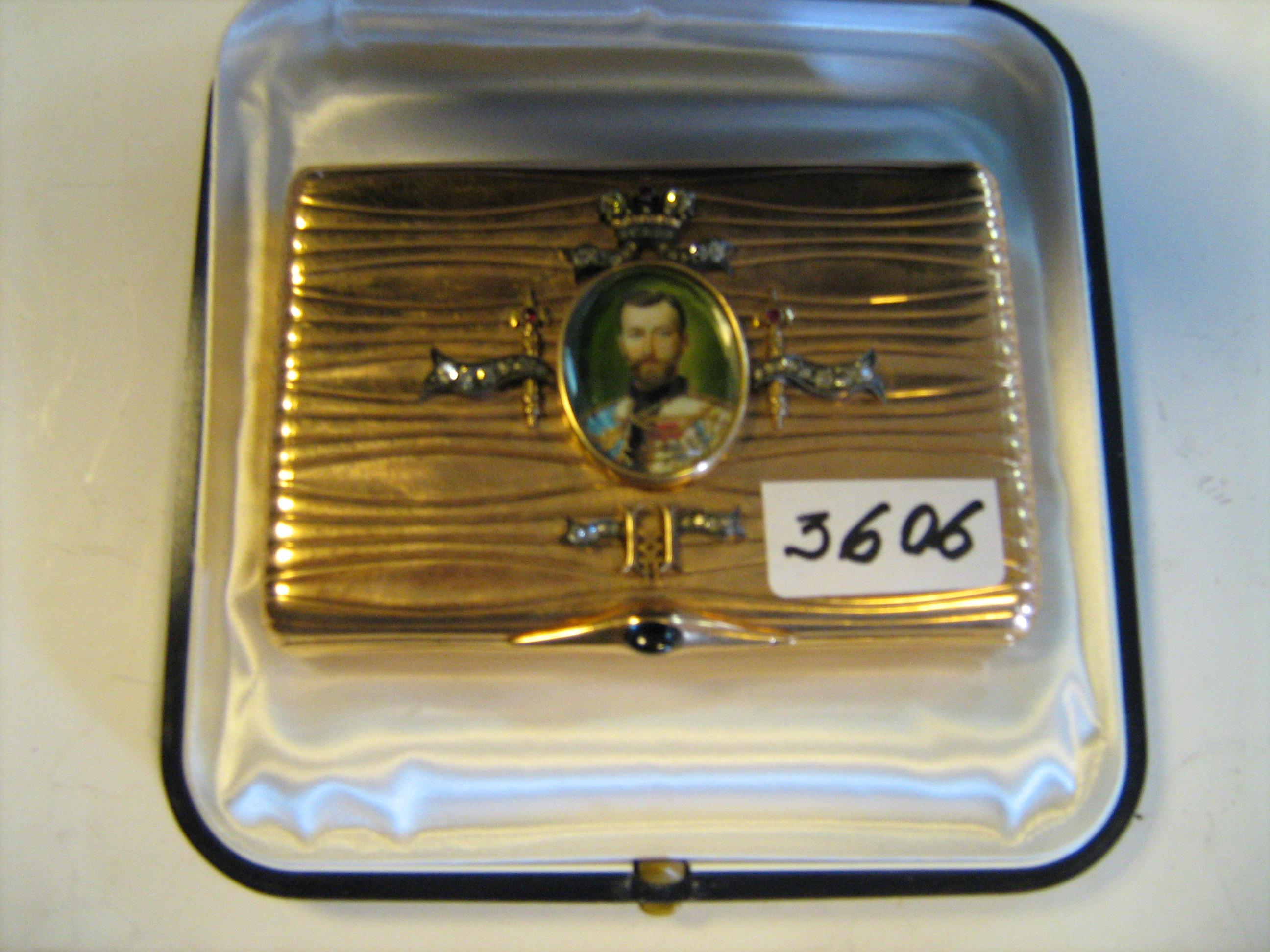 Портсигар виготовлений  із золота 56 проби з портретом Миколи ІІ, прикрашений діамантами, рубінами, сапфіром. Майстер NG - Габріель Ньюканен, який працював у фірмі К.Фаберже з 1898 р. , інв.№ 3606