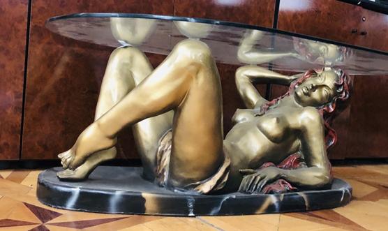 Стіл журнальний (підставка з дерева, стільниця зі скла, поміж ними лежача жіноча фігура з гіпсу, розмальована) , інв.№ 3586